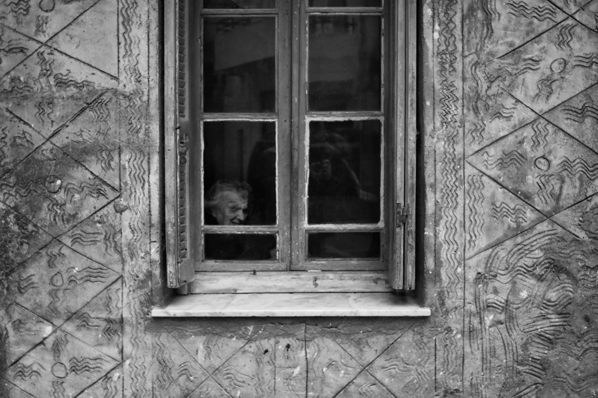 Old woman staring through a window